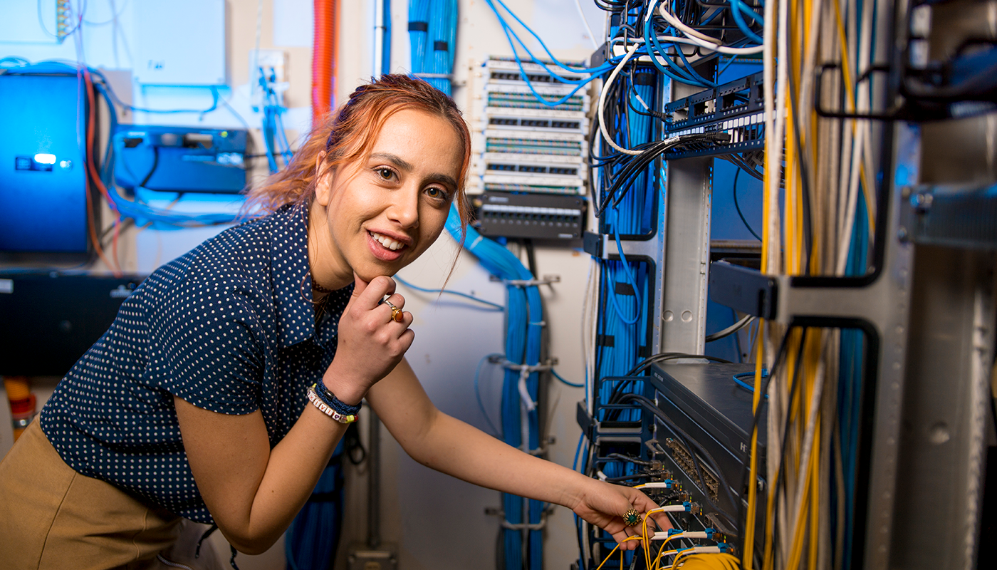 A Computer Information Systems student working on wires to servers.